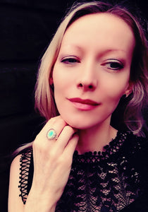 model wearing a celtic sterling silver mood ring with a blue green color meaning