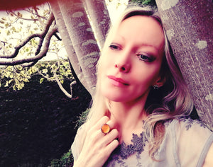 blonde model wearing a circular mood ring by a tree