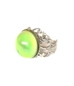 a mood ring showing a green yellow mood with a silver brass band