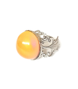 a circular mood ring turning an orange color with a silver brass band