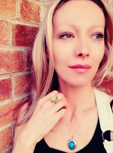 blonde model wearing a mood ring and a mood locket necklace