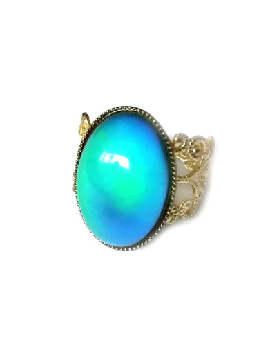 an oval mood ring with a green blue mood color set on a gold brass band