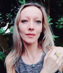 blonde model wearing an oval mood ring and a vintage mood necklace in the garden