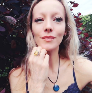model wearing a marble mood ring and a circular mood necklace outside