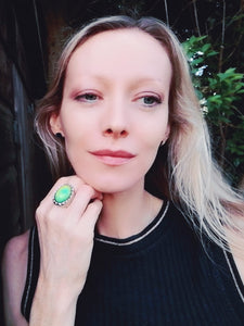 blonde model wearing a large mood ring with a green color mood