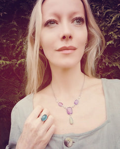 model wearing a mood ring and a mood necklace in the garden