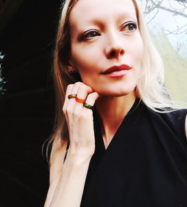 blonde model wearing a red, green and black agate mood ring
