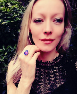 a model wearing a sterling silver mood ring with a purple color meaning