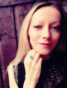 a model wearing a sterling silver celtic mood ring showing a blue mood meaning