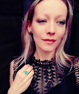 a model wearing a sterling silver mood ring showing a blue mood meaning