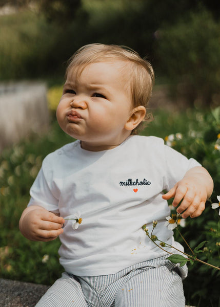 "Our organic baby t-shirt ""Milkaholic"" made of 100% premium organic cotton with 2 snap buttons on the right shoulder. Our baby t-shirts are soft like a cocoon! The baby t-shirt is white and has a navy blue embroidery ""Milkaholic"" with a red heart - on the left side - close to the heart."