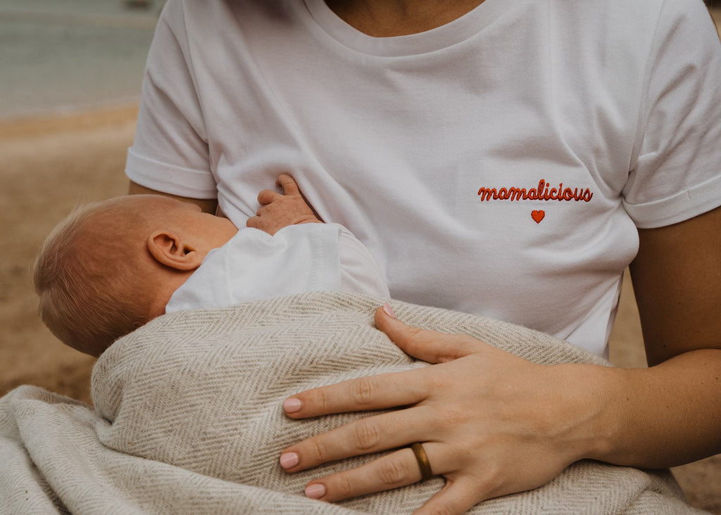 "Our organic nursing top ""Mamalicious"" made of 100% premium organic cotton has lateral openings on both sides of the t-shirt closed by easy-to-open snap buttons. Our breastfeeding t-shirts are soft like a cocoon! The nursing top is white and has a red embroidery ""Mamalicious"" with a heart - on the left side - close to the heart."