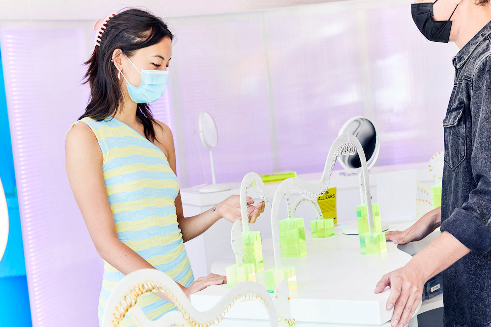 Image of a person at a counter shopping for earrings.