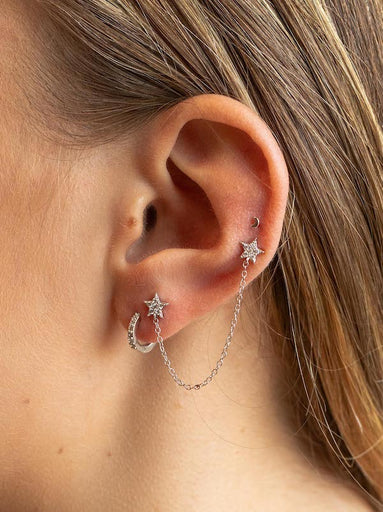 An image showing a lightning bolt dangle earring, and two other studs