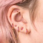 The marquise mini stud features a pink oblong shaped gem and has gold accents. color:gold/pink