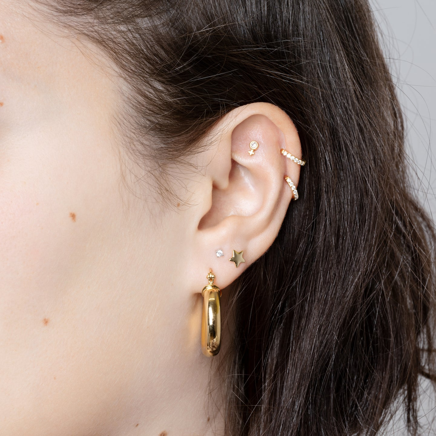 This pave venus stud represents the female / girl power and is gold with a clear gem.