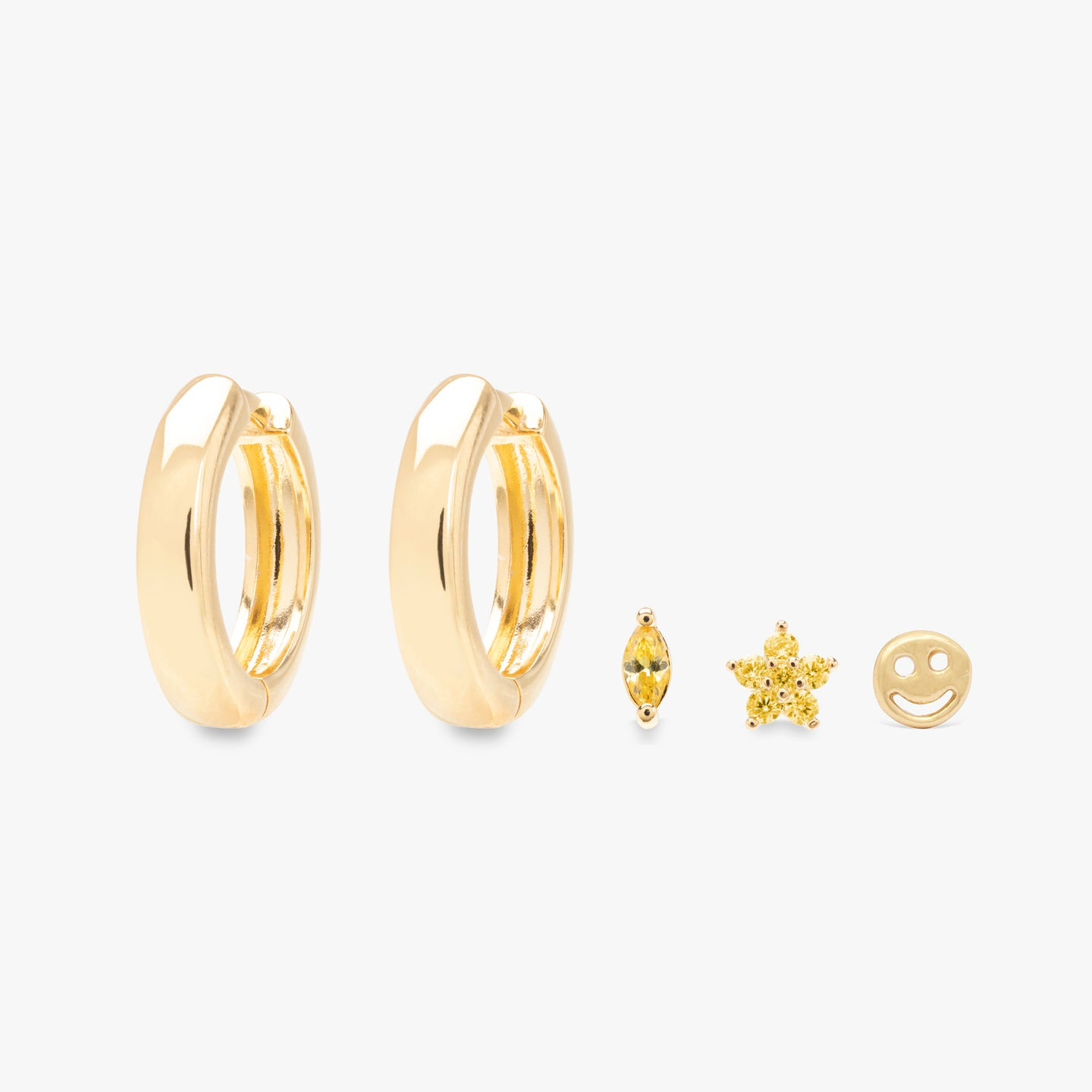 Two chunky gold hoops, one yellow CZ oblong shaped stud, one yellow CZ star stud, one gold smiley stud.