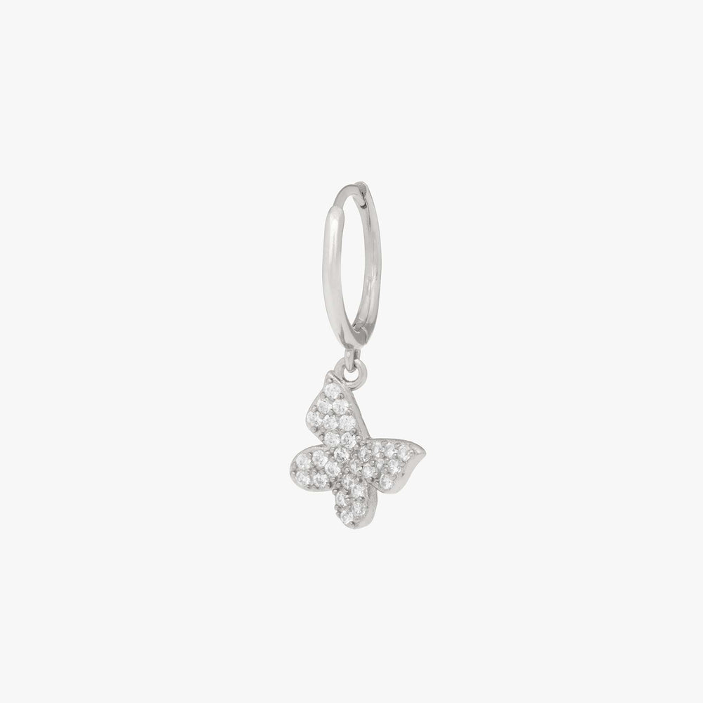 Pavé butterfly shaped charm on a silver huggie. color:silver