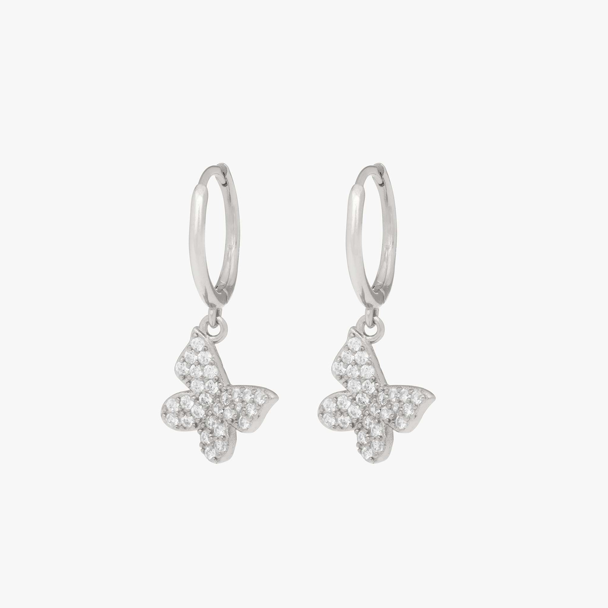 Pavé butterfly shaped charm on a silver huggie. [pair] color:silver