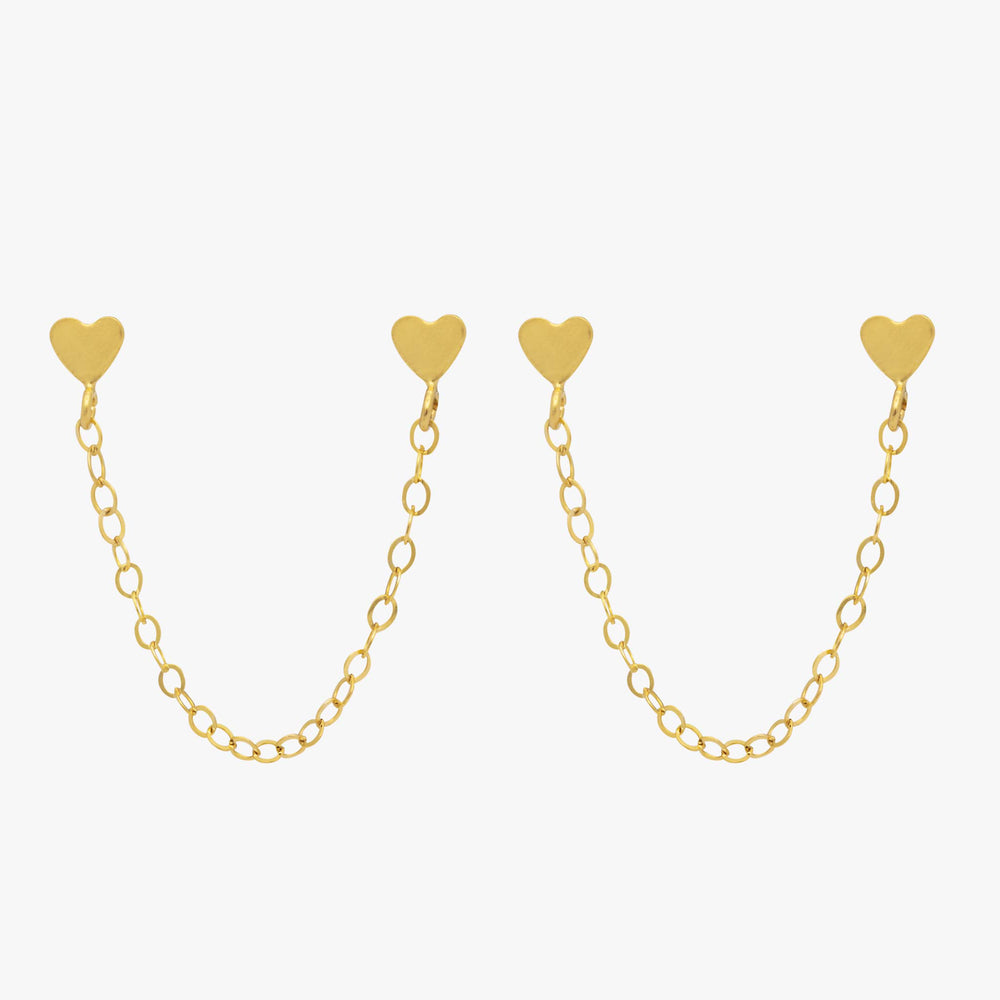 Two gold heart studs attached by a gold chain.