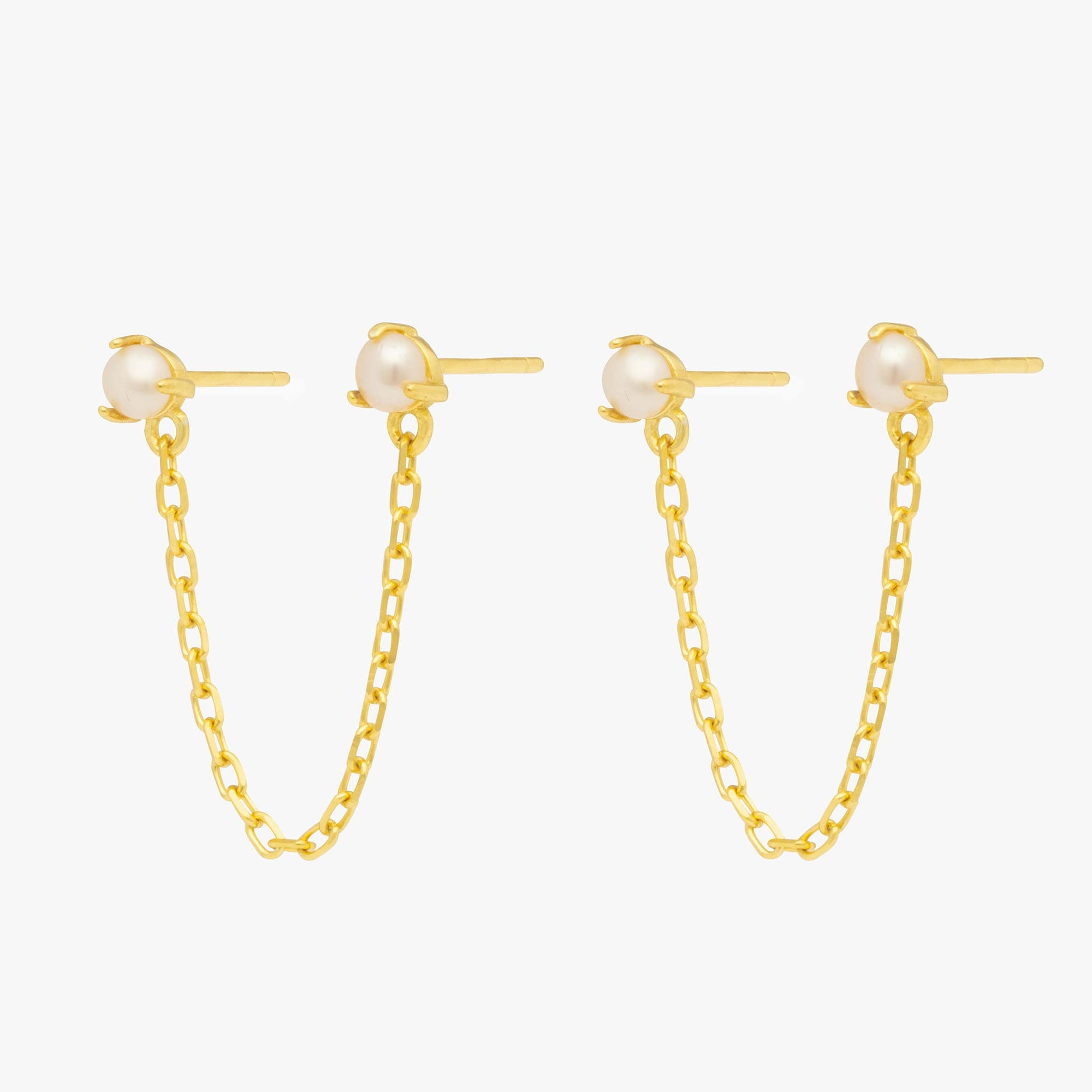 Two pearl studs linked by a gold chain.