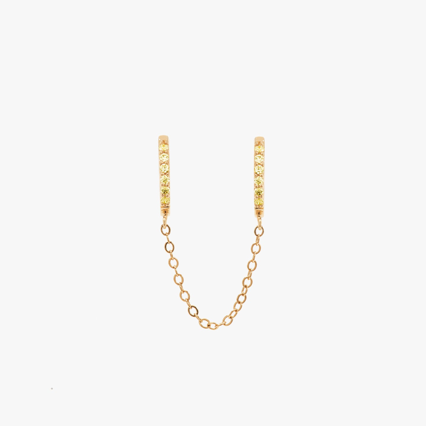 Two separate yellow CZ front huggies attached by a gold chain. color:gold/yellow