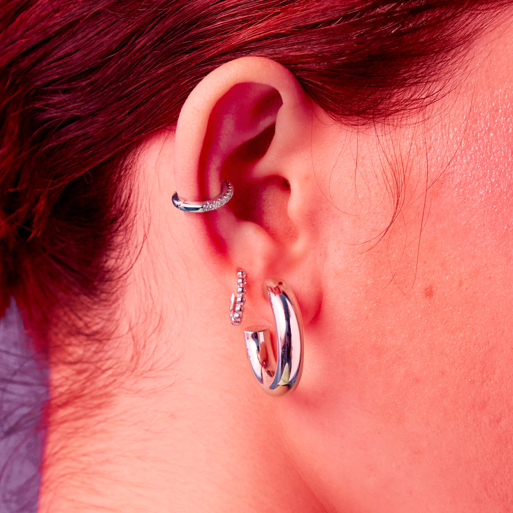 Stacked beads in the shape of a small huggie earring in silver. color:silver