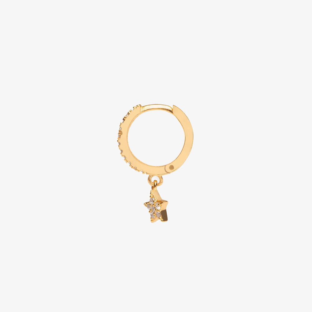 This Pave Star Huggie is a small gold hoop with a star dangle. It is covered in clear gems.
