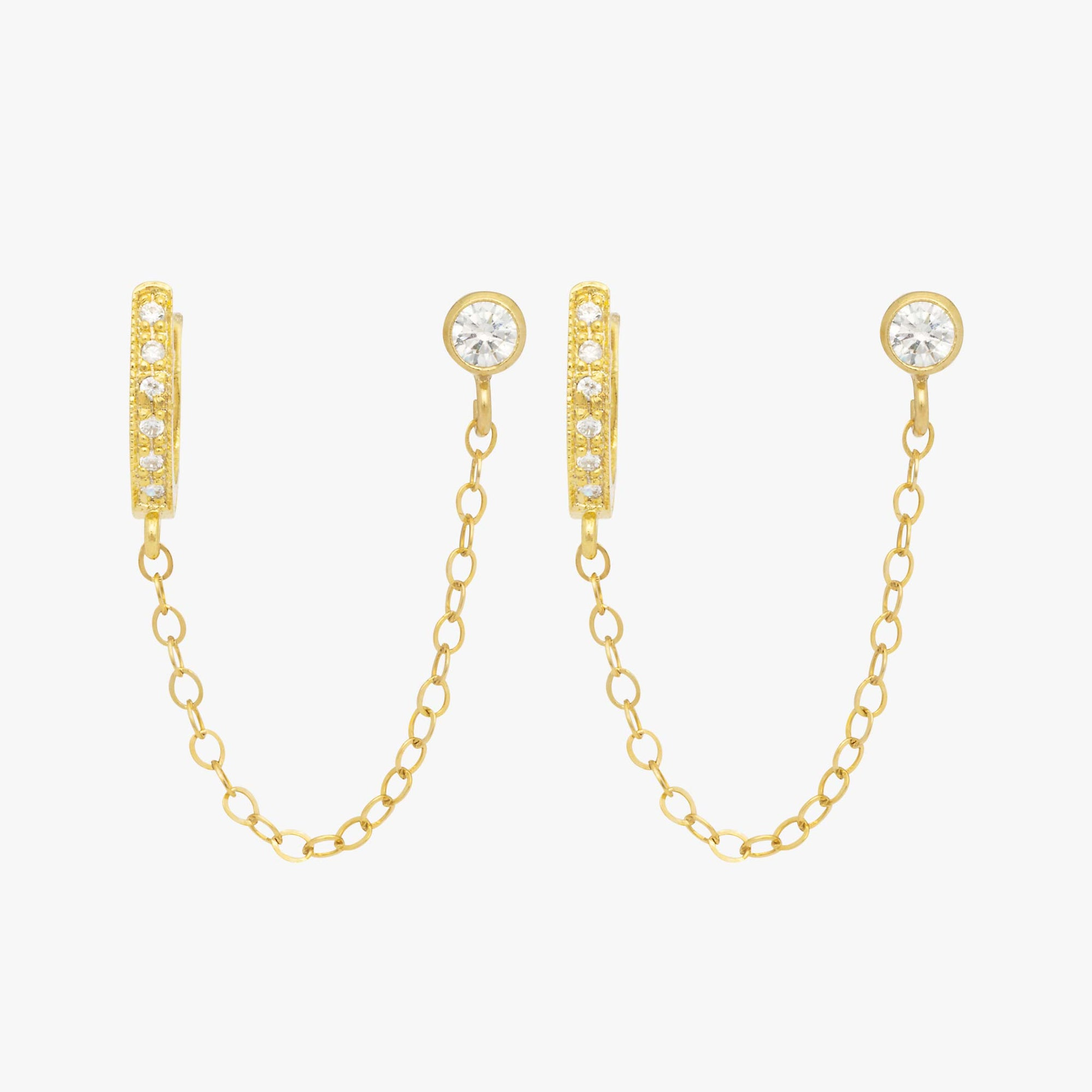 Chained gold cubic zirconia huggie and gold cubic zirconia stud.