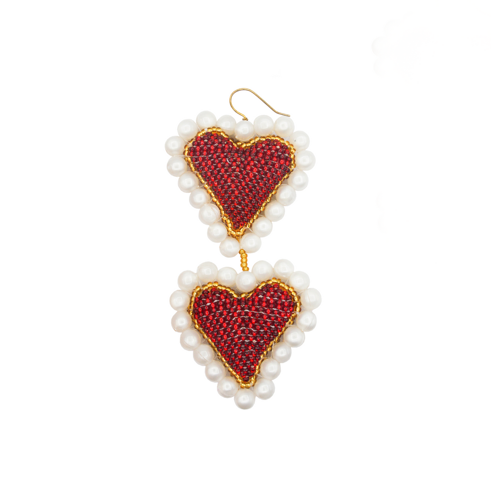 This susan alexander earring features two hearts in red and white and dangles off the ear.
