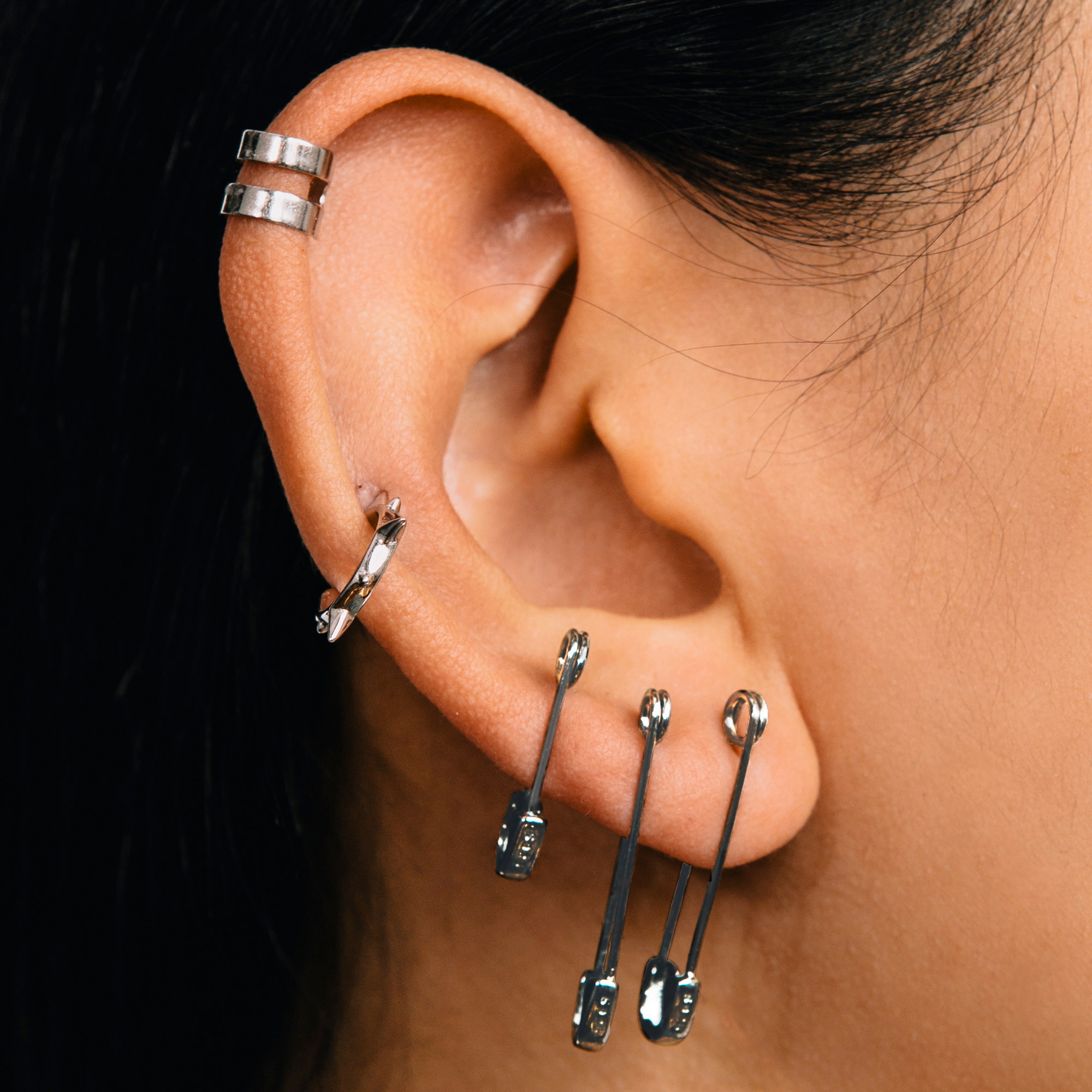The safety pin earring is a small hoop earring and comes in black and silver. color:gunmetal / small