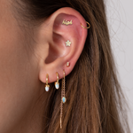 The teardrop threader is a gold chain with a opal gem on the end that dangles off the ear.