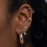 The round ear cuff requires no piercing and is a thick gold cuff.