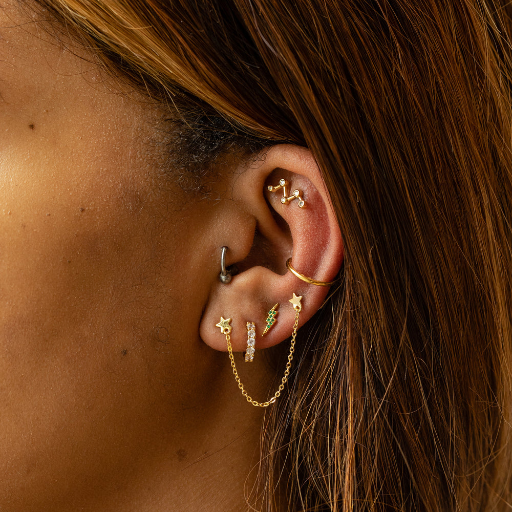 Large CZs stacked on a gold huggie earring.