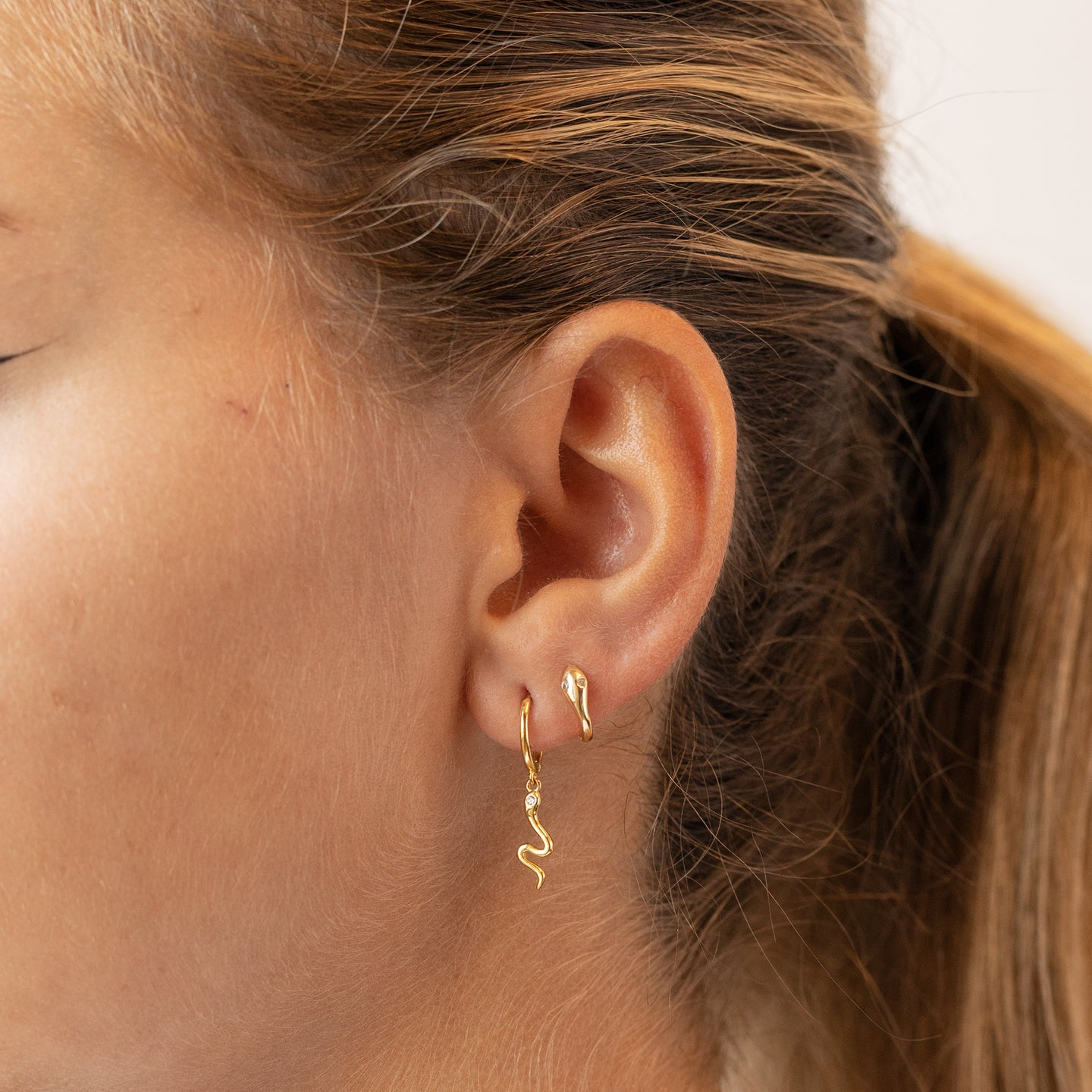 Serpent dangle in gold with a clear CZ eye on a gold huggie earring. color:gold / clear