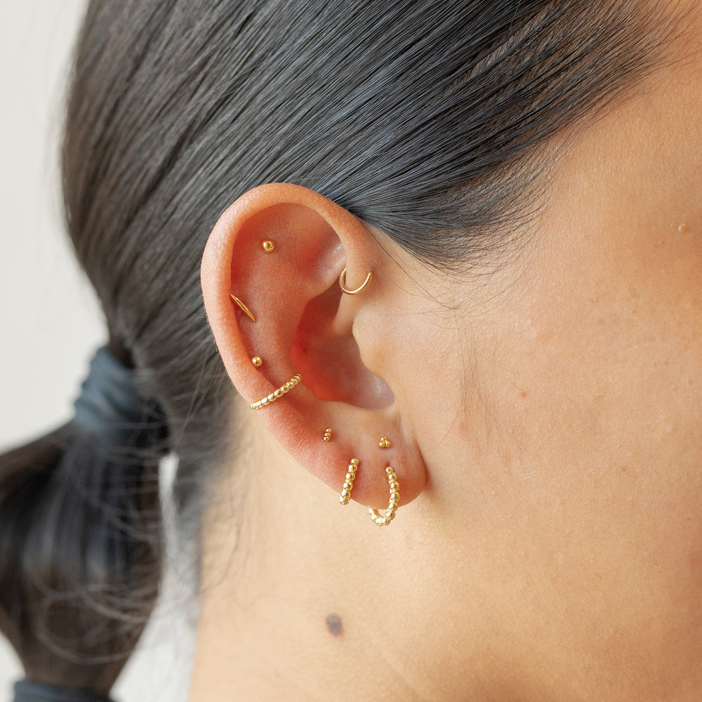 Stacked beads in the shape of a small huggie earring in gold. color:gold