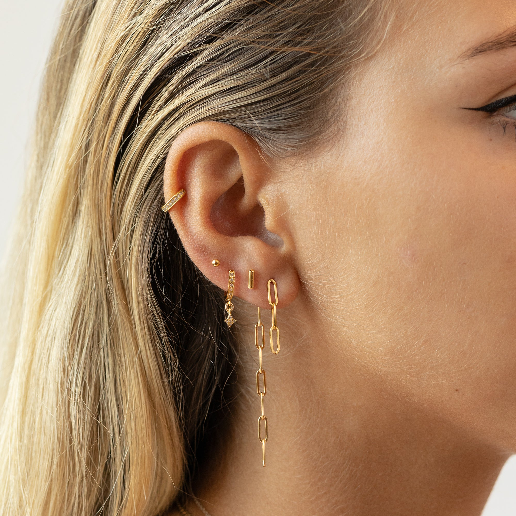 The chain jacket earring in gold is a dangle earring that hangs off the ear.