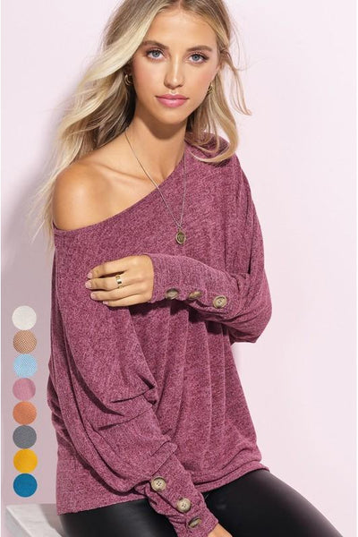 Soft Fine cotton knit top, this loose fit long-sleeve top features button details on sleeves and a tunic length, round neck line.