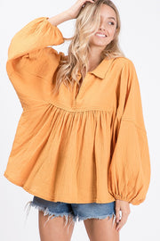 Cotton gauze fabric solid babydoll top. Features balloon long sleeve, shirring front and back, basic collar, V-neckline, raw edge detail.