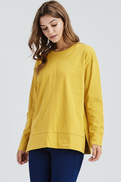 Loose fit, round neck, long sleeve top. Drop shoulder. Has waistband and banded sleeves. Has side slits. Has center back seam. Has pleat detail at bottom back hand. This top is made with a heavyweight cotton knit fabric that is soft, drapes well and has a very slight stretch.