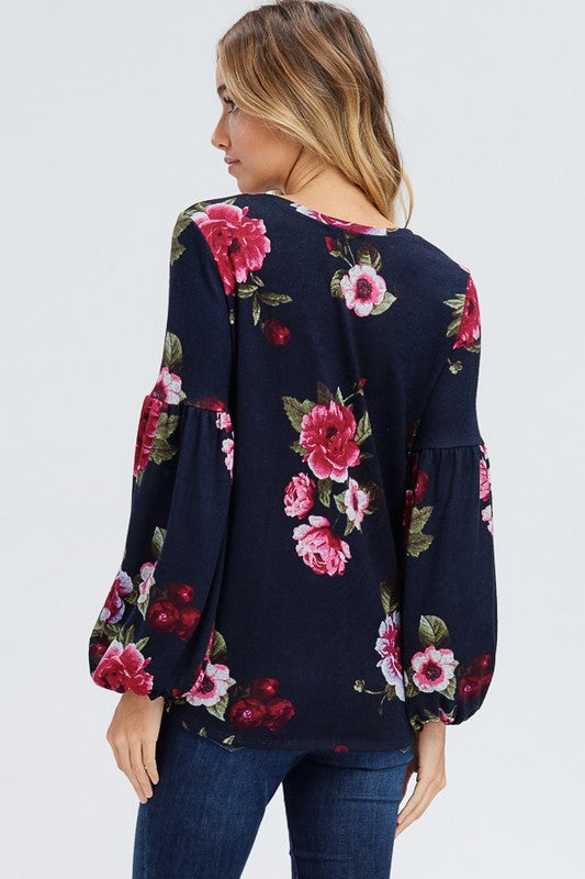 A puff sleeve floral knit sweater with a round neck featuring a front self tie knot and a hi-low hemline. Fabric is soft and comfortable.