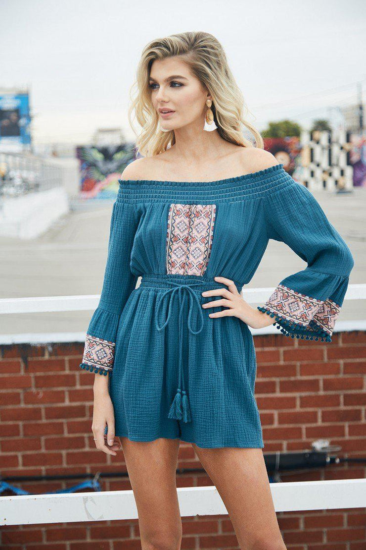 This romper features cotton fabrication with off the shoulder bodice. Elastic on the waist, bell sleeves with pom pom details. We love the embroidery design on this! Fully lined, easy fit