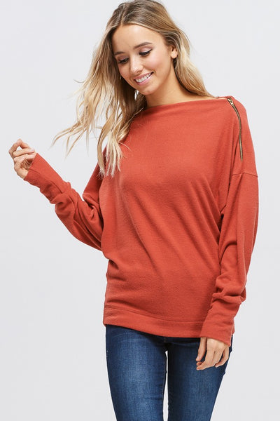 A long sleeve solid knit sweater with a boat neck featuring dolman sleeves and zipper detail. Fabric is soft and drapes well.
