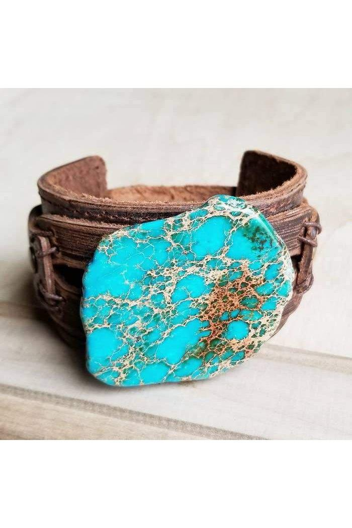 "A Genuine Slab of Regalite is attached to a Dusty Leather Cuff Bracelet.  Leather cuff measures 2"" x 9"" and is adjustable to 7"", 7.5""  Stone will vary in size from 1.5 up to 2.5"" in diameter  Although your item will resemble the photo, each piece is created by hand, so no two are identical."