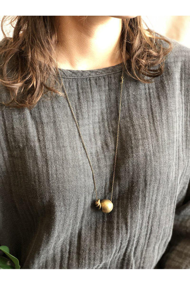 This necklace is unique in that it is a bit shorter in length than a traditional necklace which makes it perfect for layering!  Handmade in Minnesota Recycled brass beads from Ghana