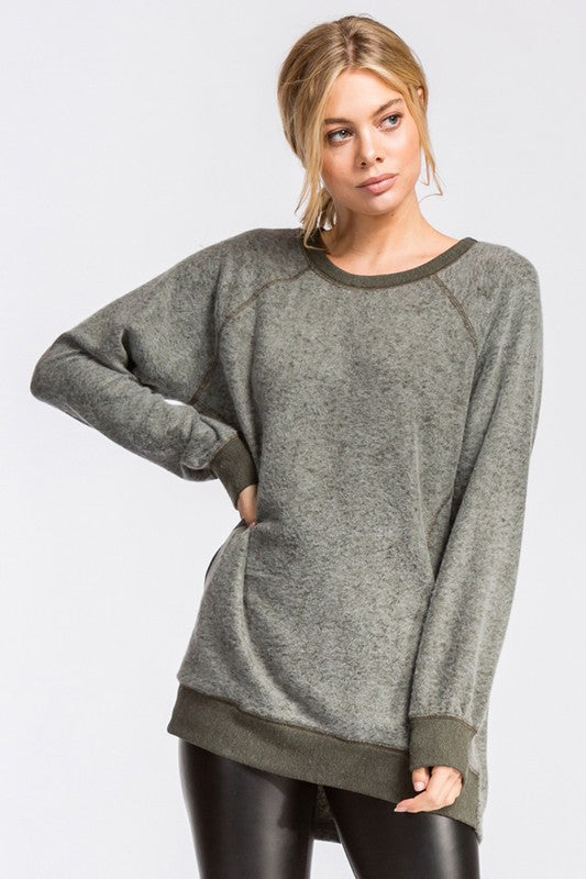 Loose fit, round neck, long sleeve raglan tunic top. Has side seam pockets, contrast neck band sleeves and waistband. The self fabric of this top is made with heavyweight brushed French terry knit fabric that soft drapes beautifully and stretches well.