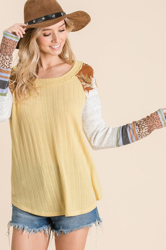 Solid ribbed knit fabric mixed matched top, Features long sleeves, boat neckline, floral and multi print knit contrast sleeve detail.  yellow boho pretty boutique