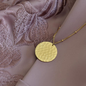 Trendy Gold Plated Coin Necklace on fabric