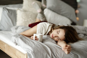 Stomach sleeping girl with coffee on bed