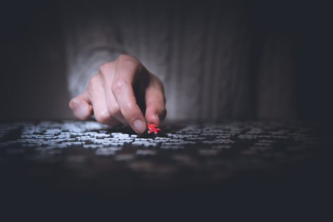 Person placing a piece of jigsaw puzzle down